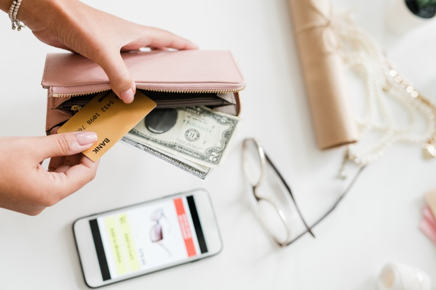 hands-young-woman-holding-nude-beige-leather-wallet-with-dollar-bills-plastic-card-smartphone-eyeglasses-desk_274679-2740